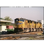 Elements of 4 railroads in 1 photo: W&A Depot, Southern Caboose, UP Locomotive pulling a CSX #X144 Intermodel train.