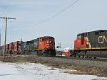 A southbound CN Q-series train (stacks) slams across Weyer Rd. as a northbound throttles up to make the trek up to the end of CN's Duplainville siding with a work crew doing something or other. Duplainville, WI. March 11th, 2011